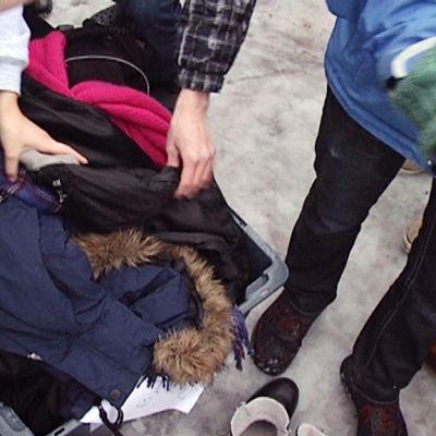 Oppilaat tutkivat tavaroitaan koulun pihalla.