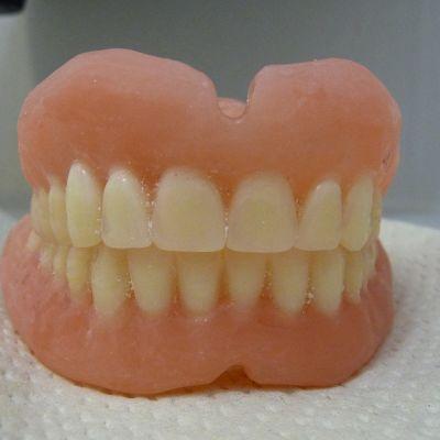 Keskeneräiset hammasproteesit hymyilevät erikoishammasteknikon pöydällä.