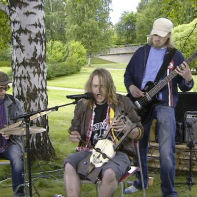 Kolmen hengen yhtye soittaa ulkona.