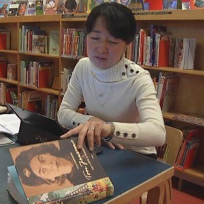 Nainen lukee kirjaa kirjastossa