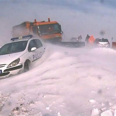 Valkoinen poliisiauto on juuttunut lumikinokseen. Takana aurauskalustoa töissä.
