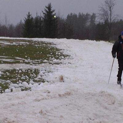 Mies hiihtää säilölumiladulla.