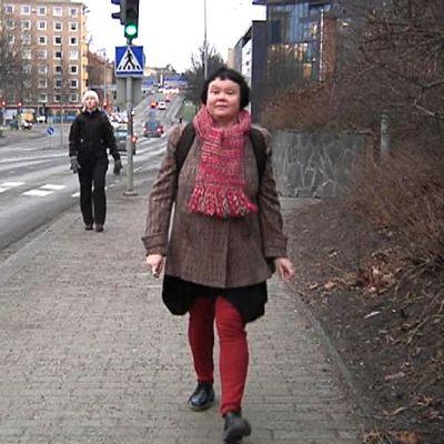 Nainen kävelee jalkakäytävällä