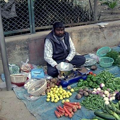 Mies istuu jlkakäytävällä ja myy kasviksia