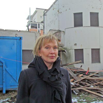Kuvassa nainen lautakasan ja ränsistyneen rakennuksen edessä