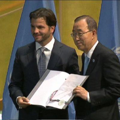 Meksikon ministeri ja YK:n pääsihteeri seisovat hymyillen rinnakkain ja pitävät yhdessä auki asiakirjaa. Miehillä on tummat puvut ja vaaleat kravatit. Takana on kaksi YK:n sinistä lippua.