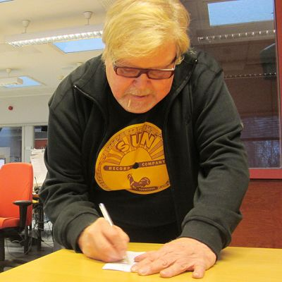 Kuvassa Jussi Raittinen kirjoittaa nimikirjoitusta