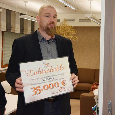 Turkistuottajain edustaja Lasse Joensuu ojentaa Keski-Pohjanmaan keskussairaalan lastenosaston ylilääkäri Andreas Blanco Sequeirosille lahjoitushekin.