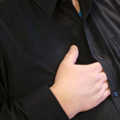 Käsi laitettu paidasta sisään.