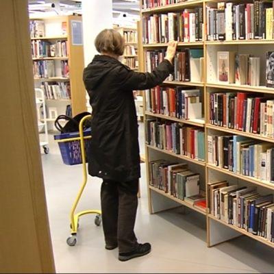 Nainen kirjaston hyllyllä