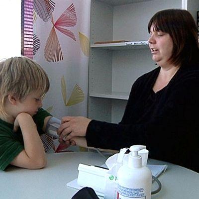 Tikkalan kylähoitaja Hanna Tiihonen mittaa ekaluokkalaisen verenpainetta.