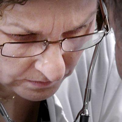 Terveyskeskuslääkäri Outi Seppälä tutkii potilasta.