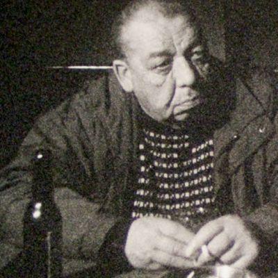 Kuvassa mies istuu pöydän ääressä tupakka kädessään