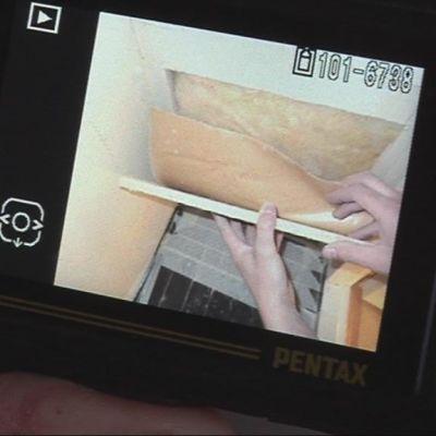 Kuntotarkastaja kuvaa tutkittavan talon seinärakennetta.
