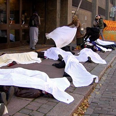 ihmisiä makaa kadulla lakanoilla peitettynä