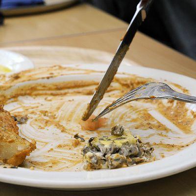 Henkilö leikkaa ruokaa lautasella.