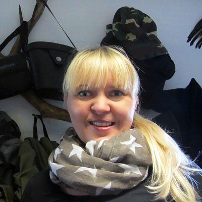 Eija Haikara, taustalla metsästystarvikkeita.