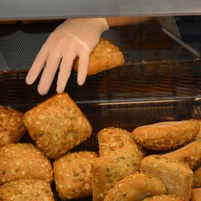 Paistopisteen leipähyllyyn lisätään vasta paistettuja sämpylöitä.