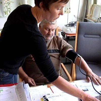 Terveydenhoitaja mittaa  verenpainetta.
