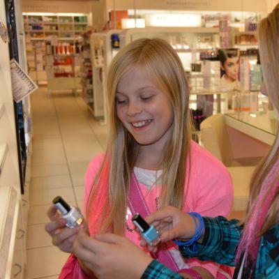 Kuvassa kaksi tyttöä tarkastelee kynsilakkoja kaupan kosmetiikkaosastolla