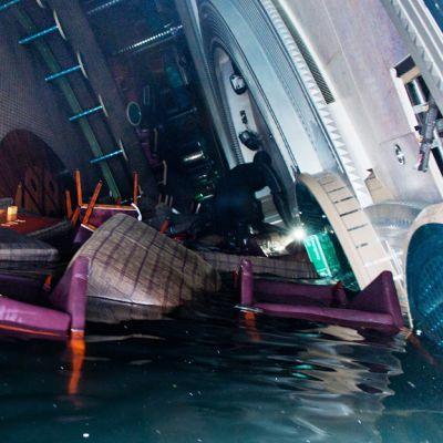Kallellaan ja puoliksi veden vallassa olevan laivan yökerho. Vedessä ajelehtii huonekaluja, joiden yli sukeltaja kiipeilee.