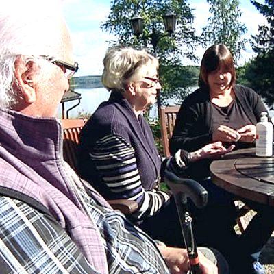 Tikkalan kylähoitaja Hanna Tiihonen mittaa Leea Pienimäen verensokeria, vieressä seuraa Seppo Pienimäki.