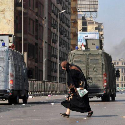 Nainen juoksee turvallisuusjoukkojen pakettiautojen vierellä.