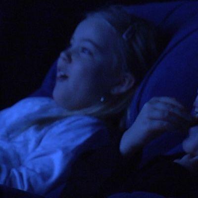 Lapset nauttivat elokuvasta elokuvateatterissa.