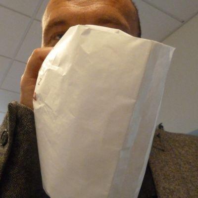 mies hengittää paperipussiin