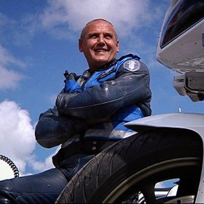 Moottoripyöräpoliisi istuu moottoripyorän päällä.