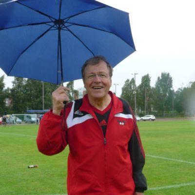 Arvi Lind sateenvarjon kanssa urheikukentällä.