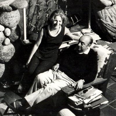 Neruda ja Urrutia takan edessä vanhan esineistön ympäröiminä.