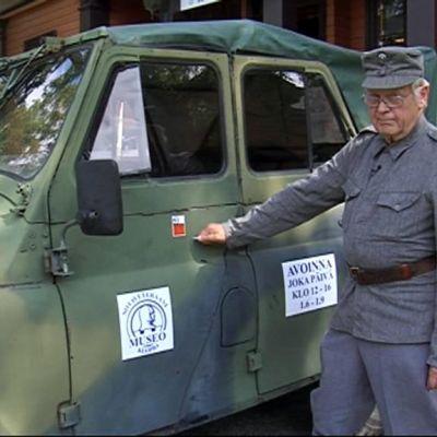 Mies esittelee vanhaa venäläistä sotilasajoneuvoa.