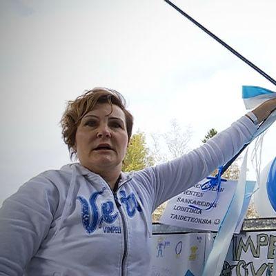 Anne Niemi kiinnittää ilmapalloja kaiteeseen