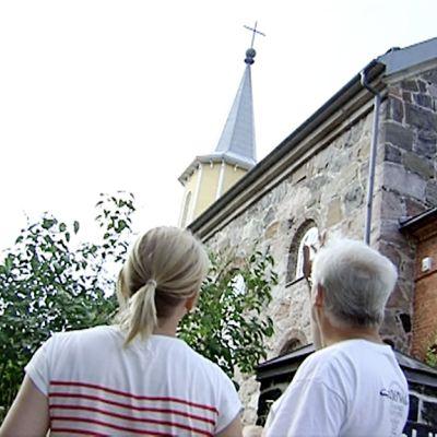 Myrskybongari osoittaa toimittajalle salamaniskun suuntaa kirkon edustalla.