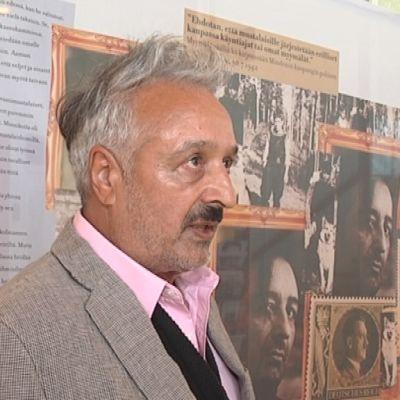 Mies seisoo kuvia sisältävän lakanan edessä