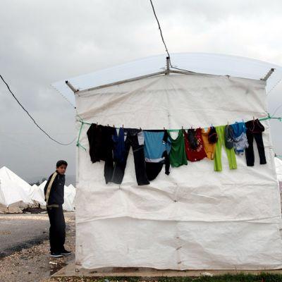 Syyriasta paennut poika seisoo teltan vieressä Turkin Hatayssa.