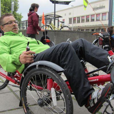Kuvassa nojakkipyöräilijä esittelee kolmipyöräistä nojapyöräänsä.