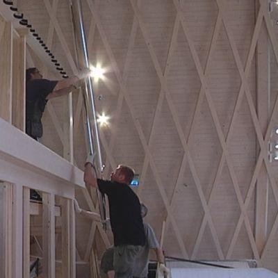 Kolme miestä rakentaa urkuja.