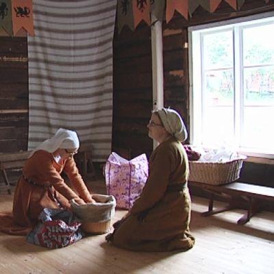 Keskiaikaisiin vaatteisiin pukeutuneet naiset touhuavat mökissä