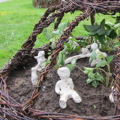Kuvassa punottu ympyräkehikko ja sen sisällä mansikan taimia sekä pieniä ihmisen muotoisia veistoksia