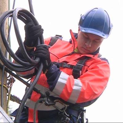 Sähköverkostoasentaja rakentaa maastokatkaisijaa.