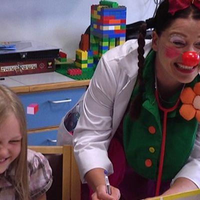 Sairaalaklovni naurattaa pikkutyttöä.