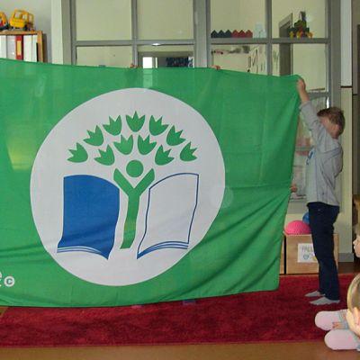 Lapset pitelevät vihreää lippua.