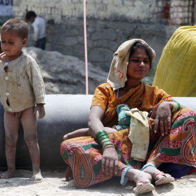 Nainen ruokki vauvaansa Srinagarin kaatopaikalla Intiassa.