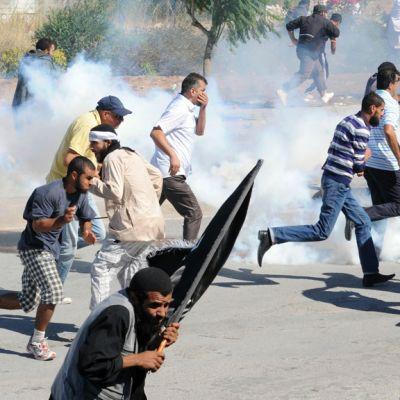 Protestoijat pakenivat mellakkapoliisia Tunisissa Yhdysvaltain lähetystön edustalla 14. syyskuuta 2012.