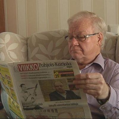 Mies lukee puoluelehteä.