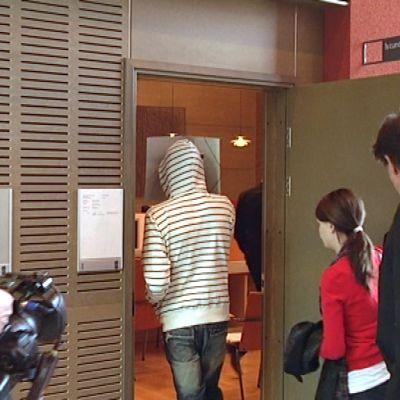 Nettivakoilusta syytetty kävelee Kymenlaakson käräjäoikeuden istuntosaliin.