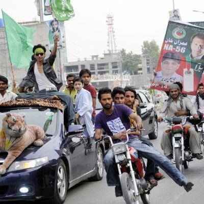 Pakistanin Muslimiliiton ( PML-N) kannattajat ajavat liput liehuen kohti äänestyspaikkaa Rawalpindissa.