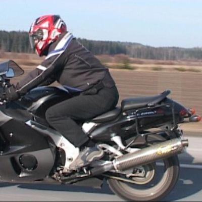 Moottoripyöräilijä ajaa tiellä